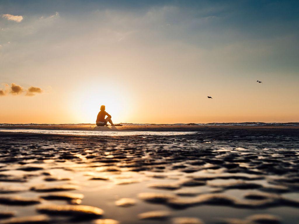 Eine Frau sitzt im Sonnenuntergang im Watt auf der Insel Norderney