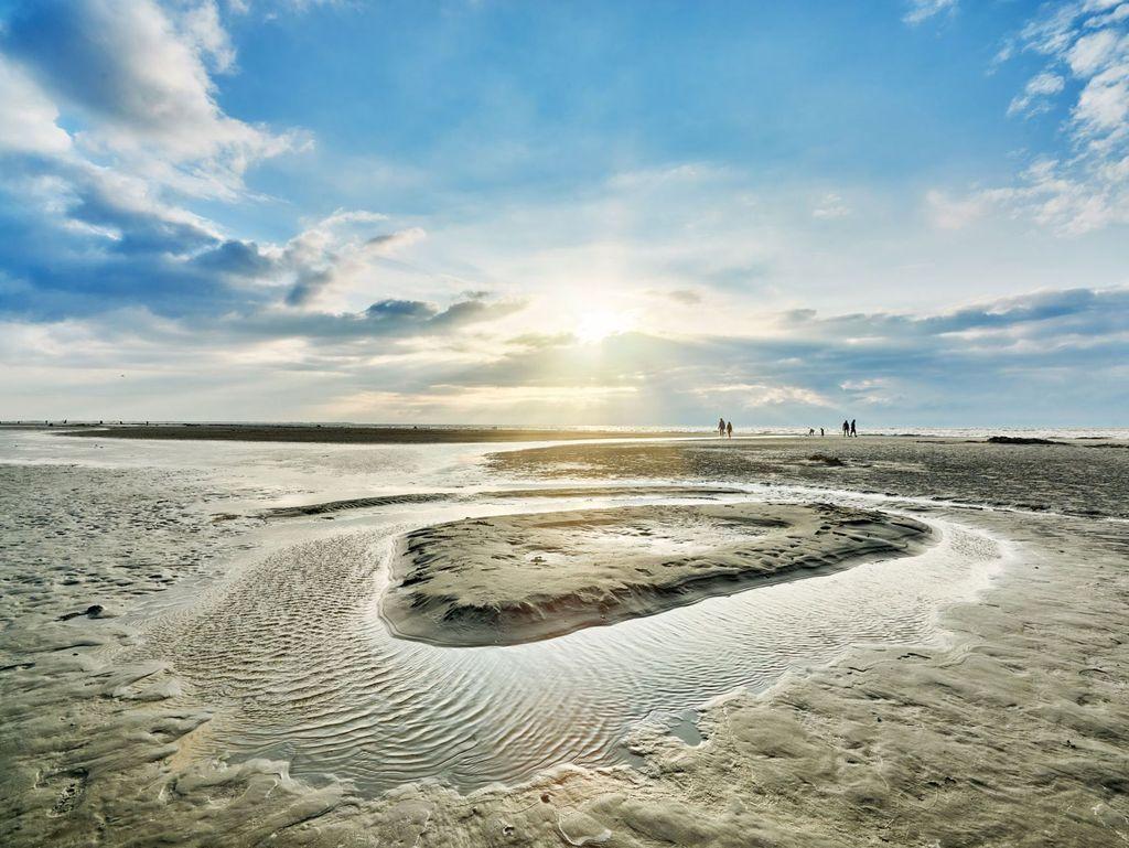 Die letzten Sonnenstrahlen über dem Wattenmeer bei Ebbe