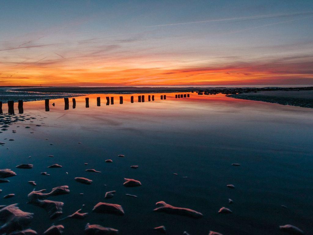 Orangener Himmel nach Sonnenuntergang über dem Wattenmeer von Norderney