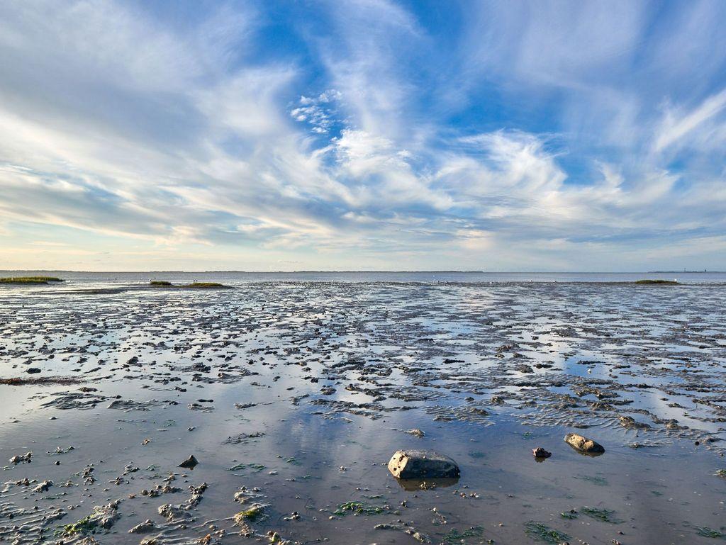 Blauer Himmel und Wolken über dem Wattenmeer bei Ebbe