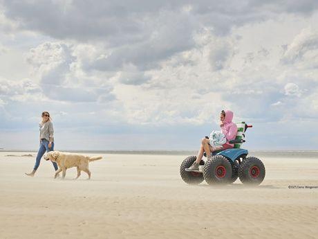 Frau fährt mit dem Strandmobil über den Strand von Langeoog